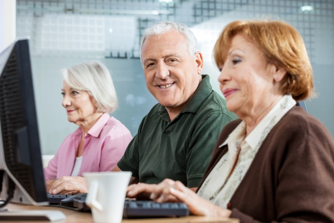 Portrait of confident senior man sitting in computer class with female friends at desk