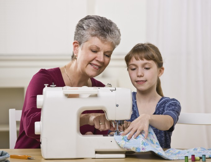 A grandmother and granddaughter using a sewing machine together. Horizontally framed shot.